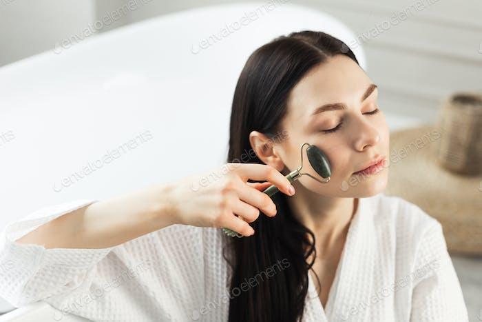 Hermosa mujer europea utiliza rodillo de jade para masajear su cara