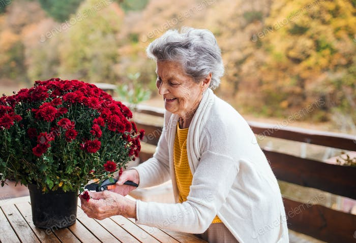 An elderly woman outdoors on a terrace on a sunny day in autumn.