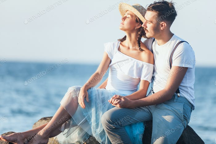 Glückliches junges romantisches Paar am Strand entspannen und den Sonnenuntergang beobachten