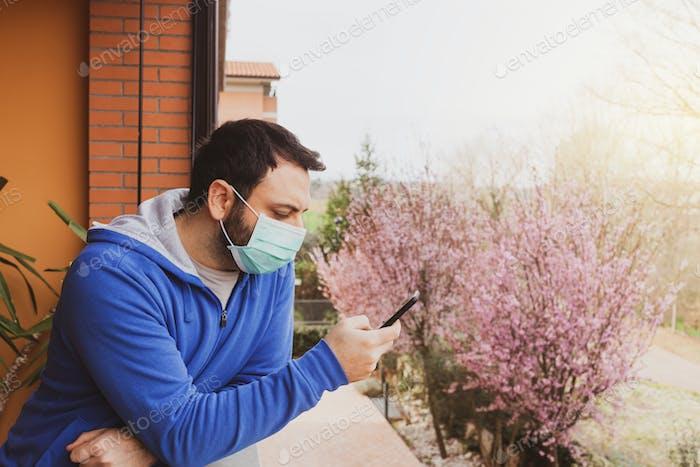 Junger kaukasischer Mann mit Maske mit Handy