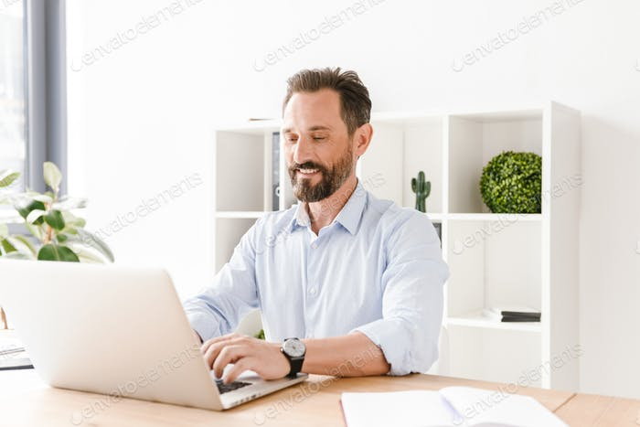 Smiling businessman working on laptop computer