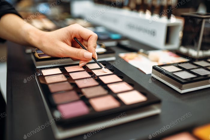 Female hand with brush, powder testing, makeup