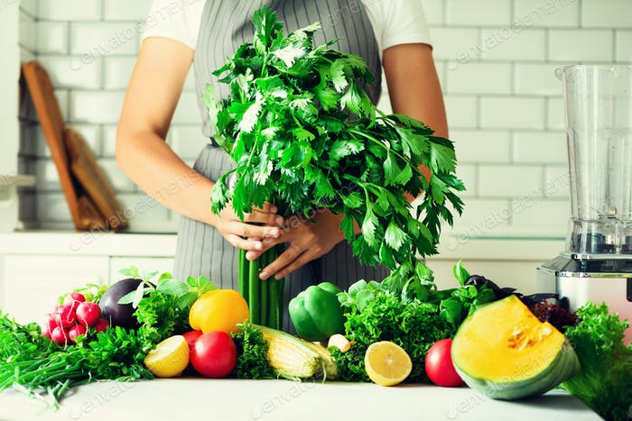 Woman hands holding fresh organic celery. vegetables, onion, tomatoes, corn, bell pepper, spinach