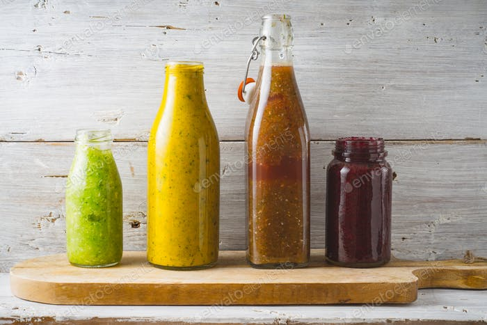 Bottles and jar with different smoothie on the white wooden background