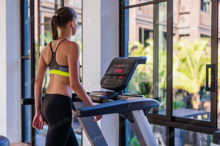 Horizontal shot of woman jogging on treadmill at health sport club at luxury resort. Female working