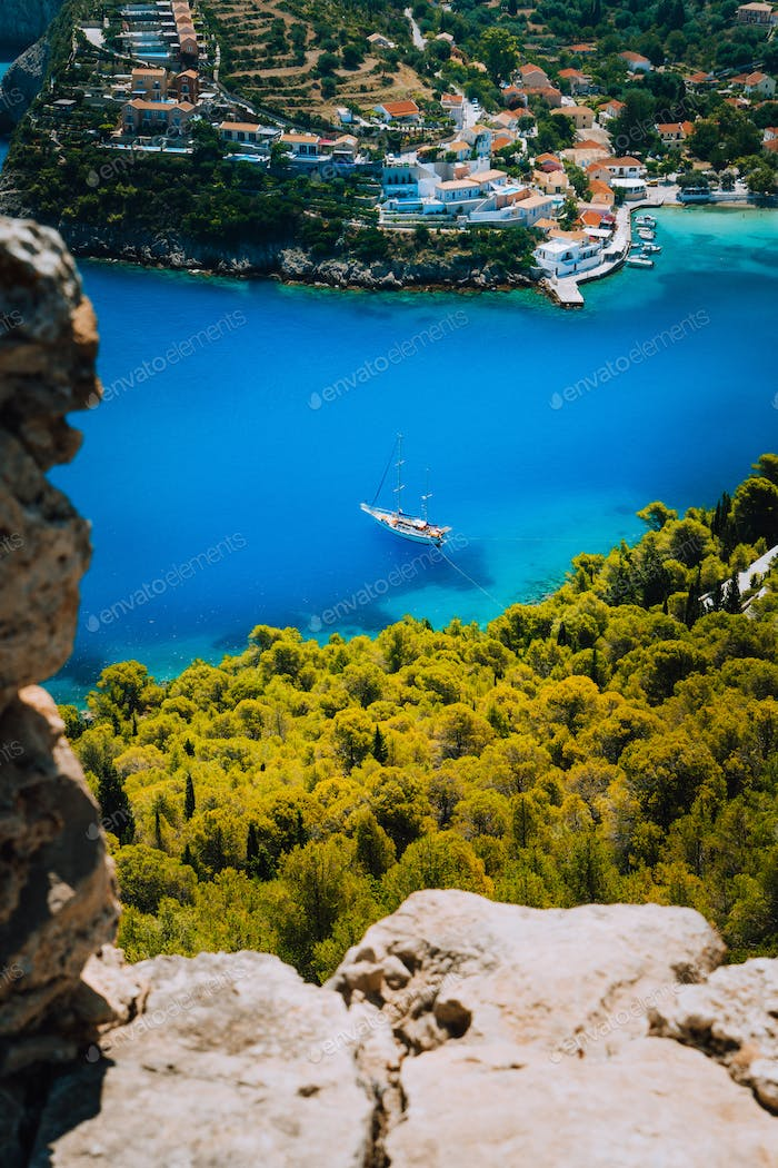 Epic view to blue bay of Assos village Kefalonia from Fortress above. White yacht at anchor in calm