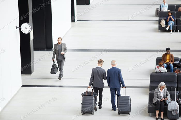 Men in suits moving along airport