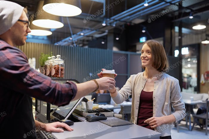 seller giving coffee cup to woman customer at cafe