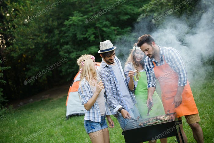 Group of friends making barbecue in the nature