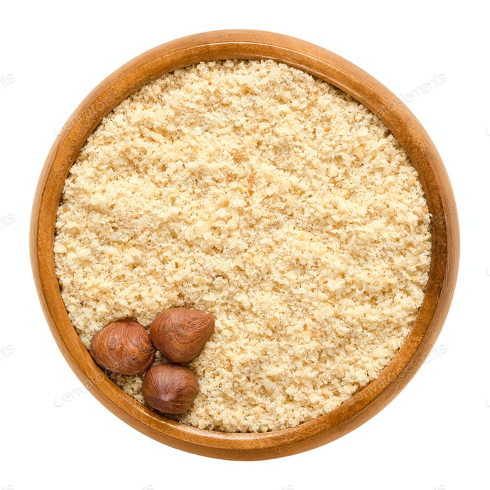Three shelled hazelnuts on hazelnut meal in wooden bowl