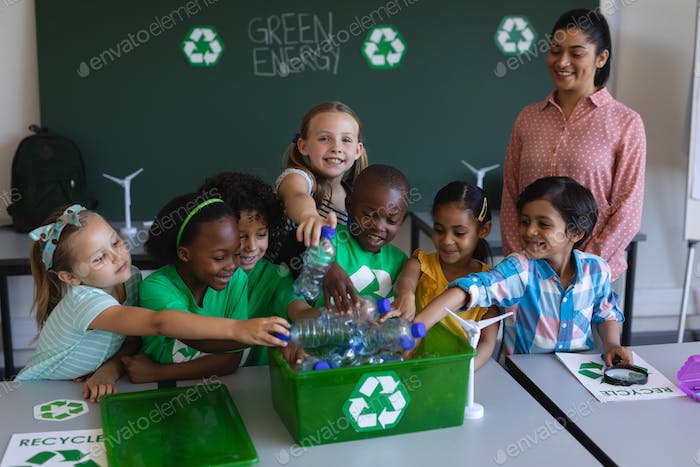 Schoolkids putting bottles in recycle container at desk in classroom of elementary school