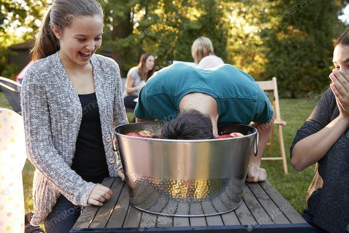Friends watch teenage boy apple bobbing at a garden party