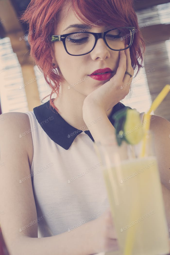 Cute hipster teenage girl in a coffee shop, retro tones