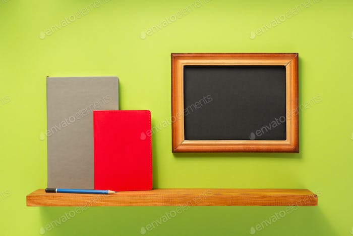books and picture frame on shelf at wall