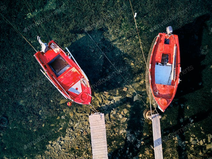 Wooden pier with fishing boats top view
