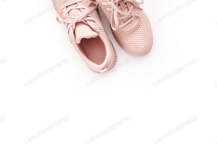 Pink female sneakers isolated on white background. Flat lay, top view