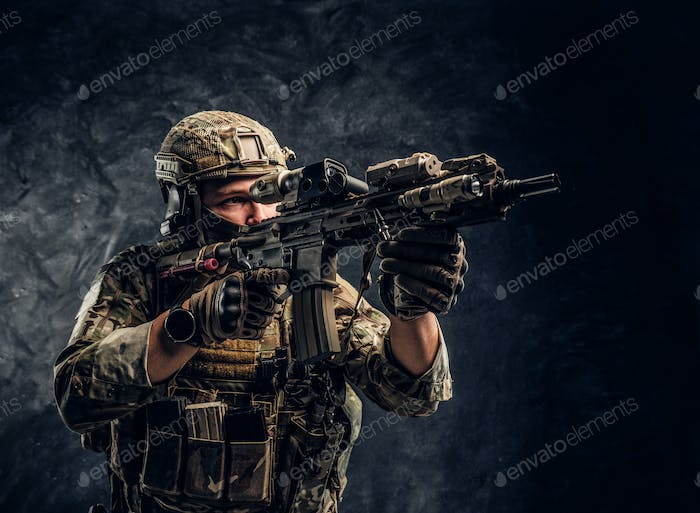 Fully equipped soldier in camouflage uniform holding an assault rifle