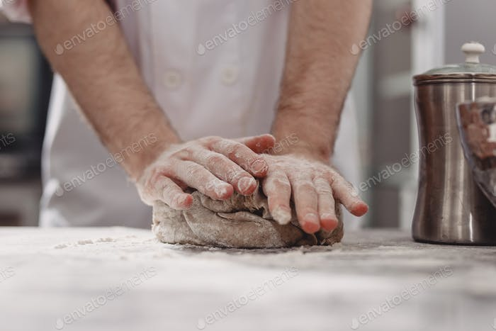 Professional baker kneads dough on the table in the kitchen of the bakery