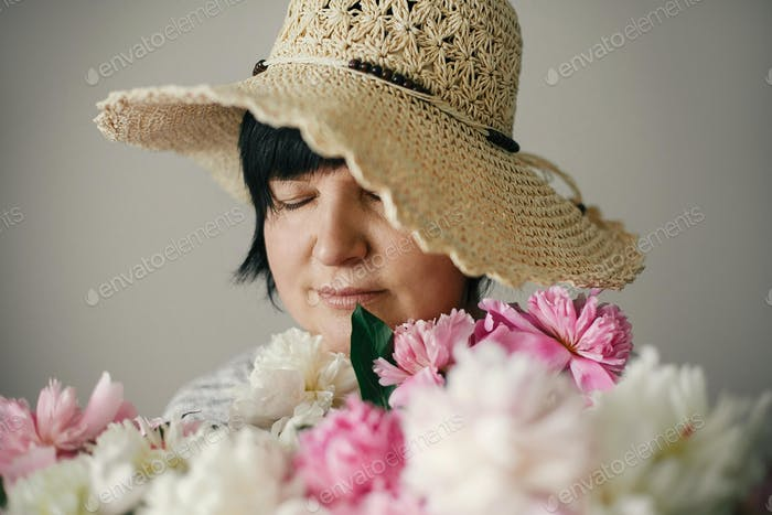 Beautiful elder woman in hat posing with many peony flowers