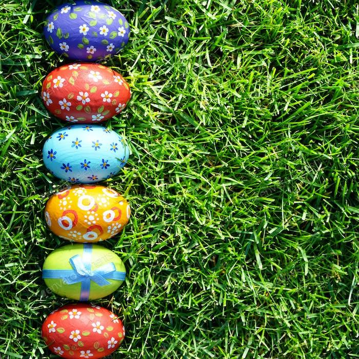 Easter eggs lying on green spring grass arranged in one lane. Sp