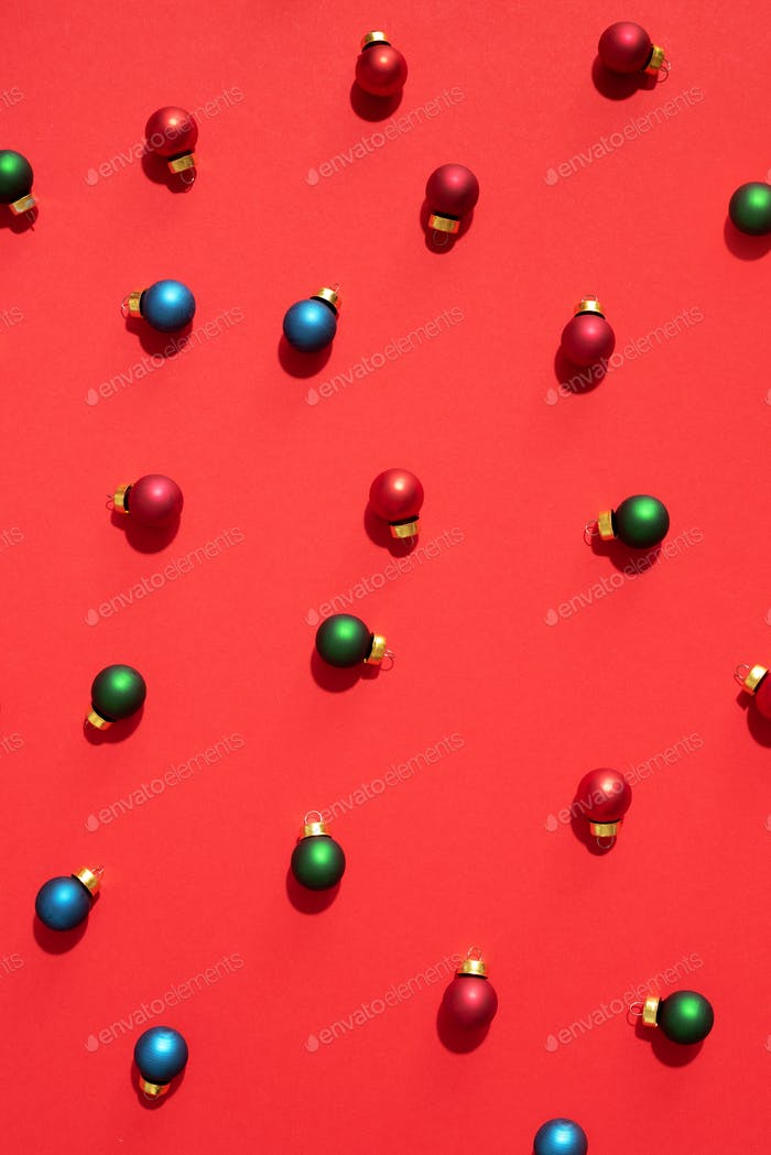 Christmas colored baubles. Festive pattern made of new year baubles on red background. Flat lay, top