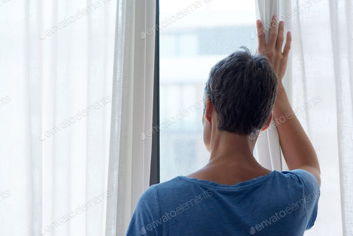 behind of middle age woman looking out window
