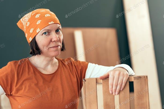 Stolze weibliche Tischlerin posiert mit fertig Holzkiste