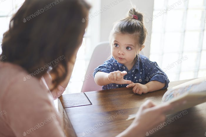 Cute girl with mom reading a book