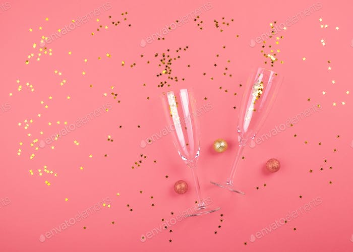 Champagne glasses with golden confetti on pink