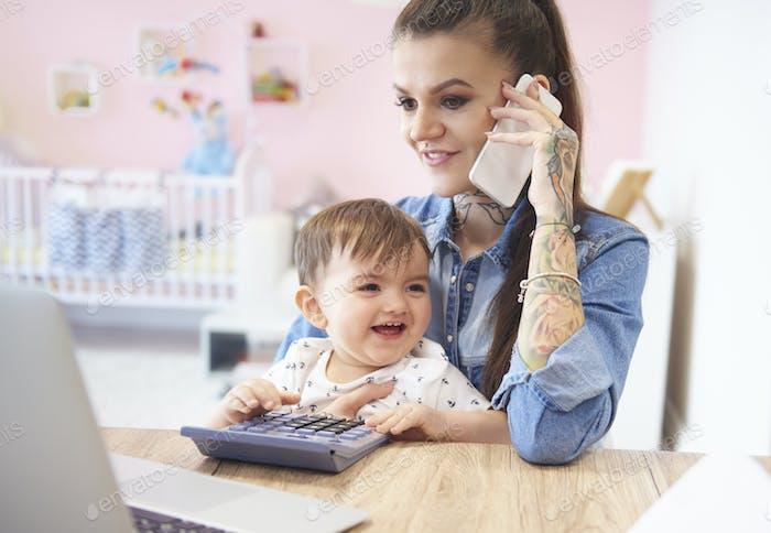 Entzückende junge mit Mama zu Hause office