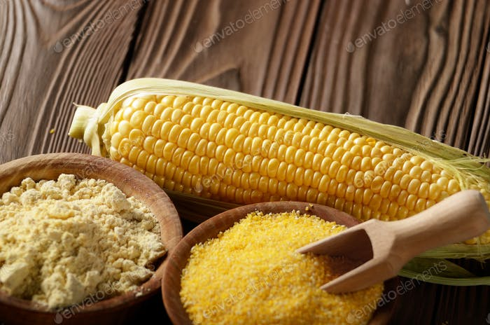 Bowl of corn grits corncob and corn flour on kitchen table