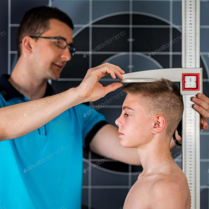 Physical Therapist measuring height of teenage boy