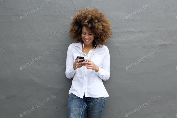 Happy african woman listening music on her cell phone