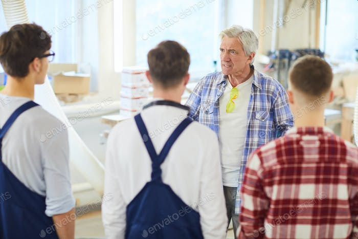 Angry carpenter yelling at young employees