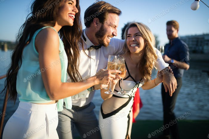 Group of friends drinking, chatting and having a fun at outdoor party