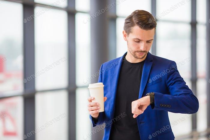 Urbaner Mann mit Kaffee im Flughafen. Ein junger Mann kommt zu spät zu einem Flug und schaut auf seine Uhr