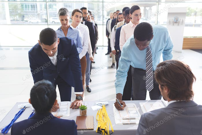 Front view of diverse business people checking in at conference registration table in office lobby