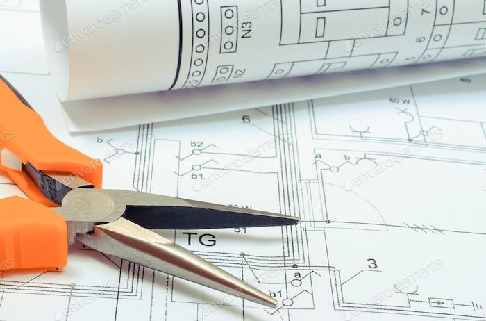 Electrical diagrams and pliers on construction drawing of house. Building home concept