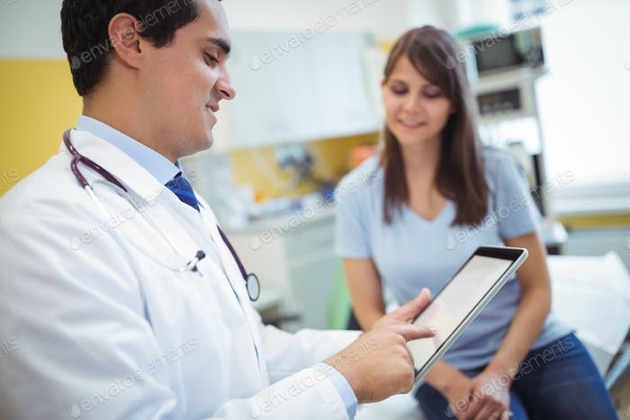 Doctor using digital tablet while consulting patient