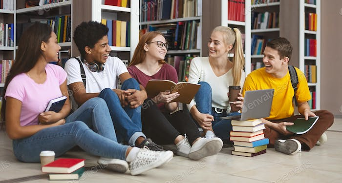 Cheerful girl telling her friends funny story, sitting at library