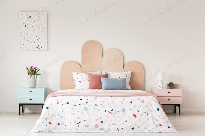 Patterned bed with headboard between pink and blue cabinet in be