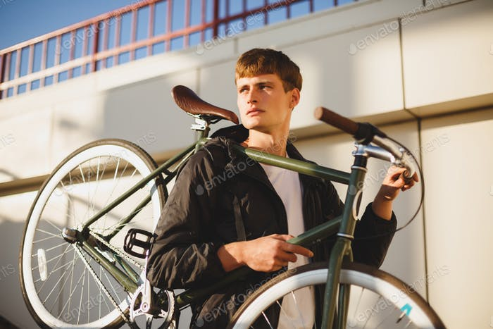 Thoughtful boy with brown hair standing and holding bicycle while dreamily looking aside