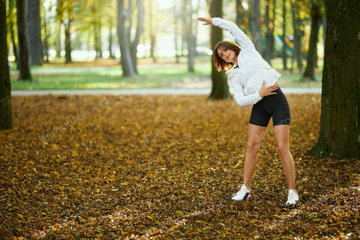Beautiful woman in activewear warming up at park