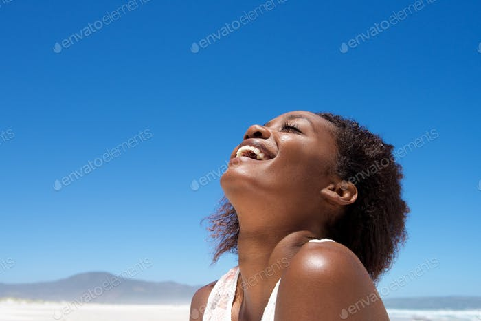 Beautiful young african woman laughing outdoors
