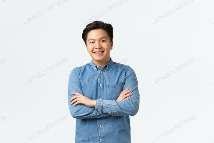 Smiling asian guy looking happy at camera, cross arms chest confident. Korean student enrolling