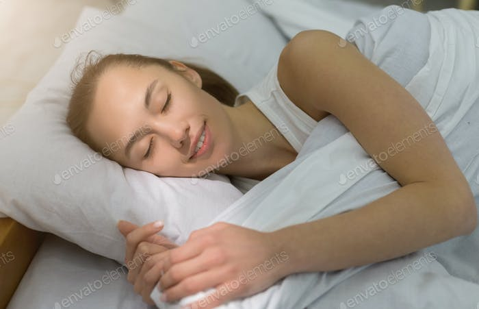 Beautiful young woman sleeping in bed comfortably