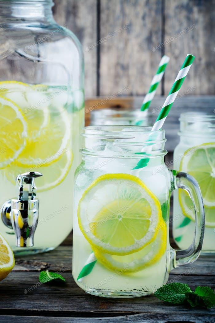 Homemade lemonade with mint, ice, and fresh lemon slices in mason jar
