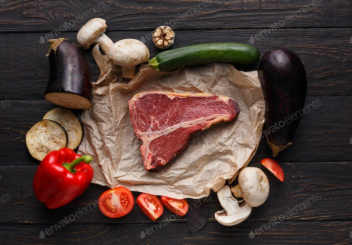 Raw t-bone steak on craft papper on dark background