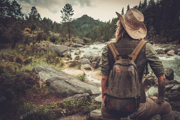 Beautiful woman hiker walking near wild mountain river.