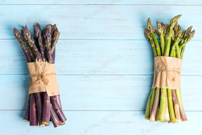 Fresh natural organic two bundles of green and purple asparagus vegetables on a blue wooden